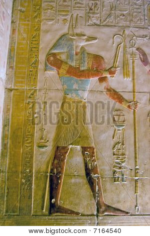 Large, painted, hieroglyphic carving of the ancient egyptian god Anubis.  Depicted with the head of a jackal, Anubis is the god of mummification. Ancient carving on an inner wall of the Temple to Osiris at Abydos, Egypt. poster