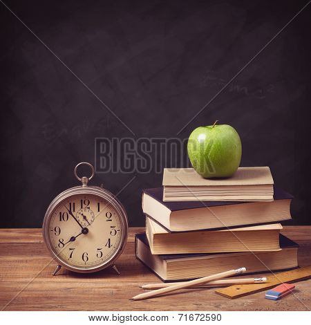back to school concept with old schoolbooks, alarm clock and apple against a chalkboard background