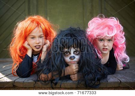 Three Halloween witches looking at camera sulkily