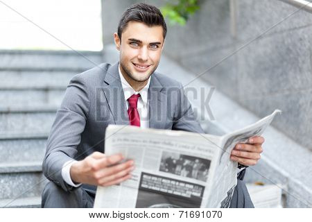 Business man reading a newspaper sitting on the stairs