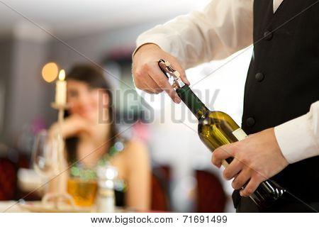 Waiter uncorking a wine bottle in a restaurant