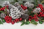 Traditional christmas background with holly, ivy, mistletoe, fir and pine cones and bauble decorations with snow. poster