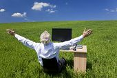 Business concept shot showing an older male executive arms raised using a computer in a green field with a blue sky complete with fluffy white clouds. Shot on location not in a studio. poster