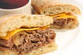 Roast Beef dip sandwich with cheese and au jus. poster