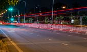 Long exposure photo of light trails on the street in Thailand. poster