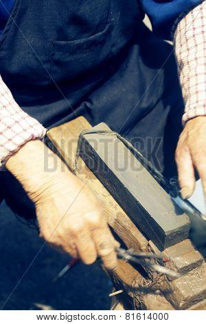 craftsman sharpen scissor with whetstone