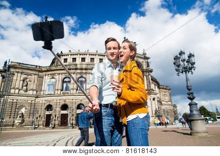Tourist couple at Semperoper in Dresden taking selfie with phone on stick poster