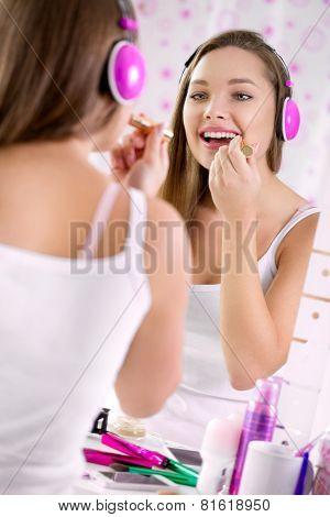 Teenage girl applying make up and looking in the mirror, pretty teens having fun and putting makeup lipstick or lip gloss, joyful teenager