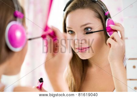 Trendy teen girl makeup and listening music