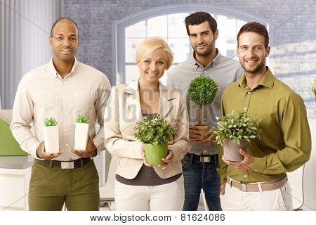 Happy environment friendly businessteam smiling, holding green plants, looking at camera.