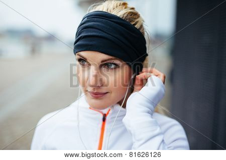 Sportswoman Wearing Headband And Listening To Music On Earphones