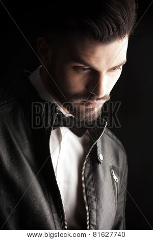 Close up picture of a fashion business man wearing a leather jacket while looking down, on dark studio background.