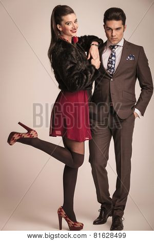 Gorgeous elegant woman leaning on her lovers shoulder and lifting one leg up while he is holding his hands in pockes.