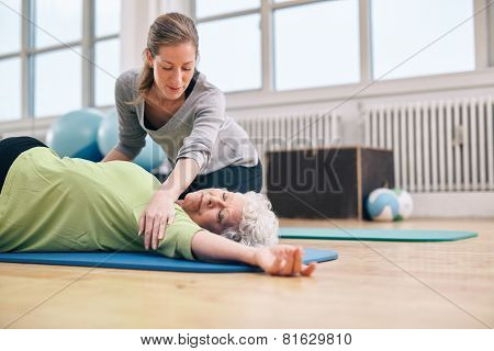 Female Trainer Helping Elder Woman In Stretching