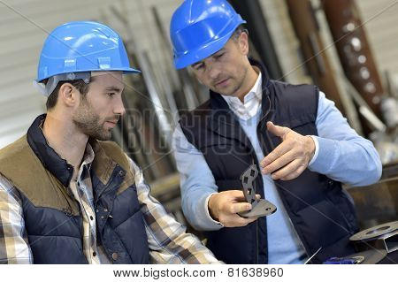 Engineer with mechanical worker checking on production