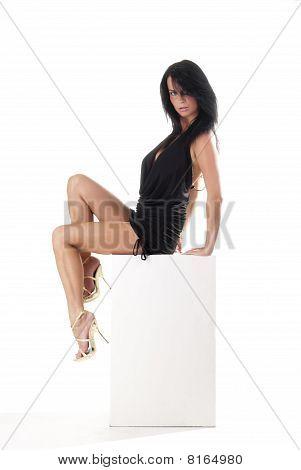 beautiful lady sitting on a white cube