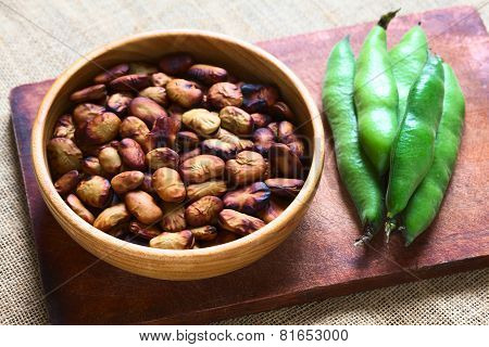 Roasted broad beans (lat. Vicia faba) eaten as snack in Bolivia in wooden bowl with fresh broad bean pods on the side photographed with natural light (Selective Focus Focus one third into the roasted beans) poster
