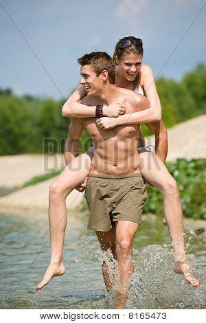 Piggyback - Happy Couple Enjoy Sun At Lake