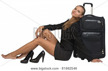 Businesswoman with her shoes off sitting hand resting on the floor, next to front view suitcase