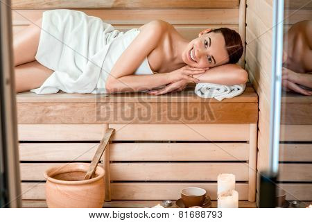 Young woman in white towel lying in Finnish sauna. poster