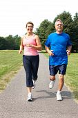 Happy elderly seniors couple jogging in park poster