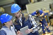 Engineers in steel factory working on digital tablet poster