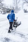 Man on the street removing snow with a snow blower. poster