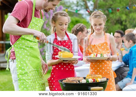 Family having barbecue at garden party, dad is putting corn and grilled vegetables on plates of daughters