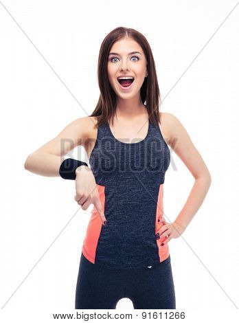 Surprised fitness woman pointing finger down isolated on a white background. Looking at camera