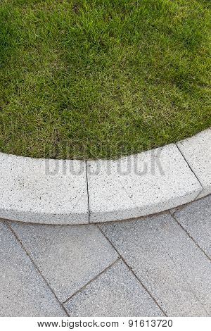 Grey Stone Paving & Kerb Adjacent To Green Grass Lawn