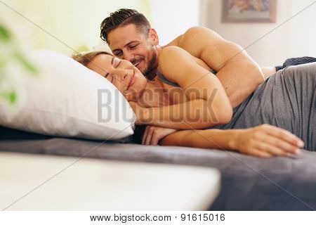 Enamored Young Couple Lying On Bed