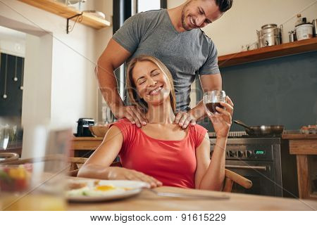 Happy young woman sitting at breakfast tablet holding cup of coffee getting a shoulder massage from her boyfriend. Young couple in morning with boyfriend rubbing girlfriends shoulders in kitchen. poster