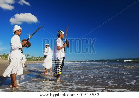 Balinese Men With Ritual Swords On The Sea Shore