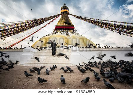 Bodhnath Stupa With Flying Birds And People Hope At Blue Sky In Kathmandu Valley, Nepal.