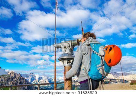 Young woman looking through binoculars, Dolomites