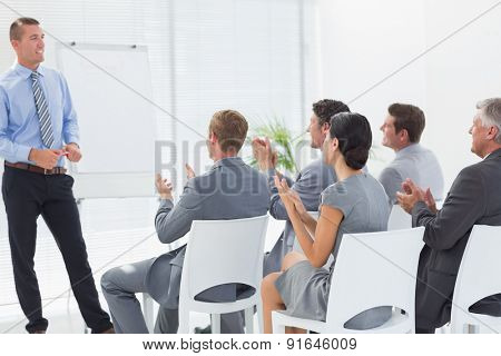 Smiling business team applauding during conference in meeting room