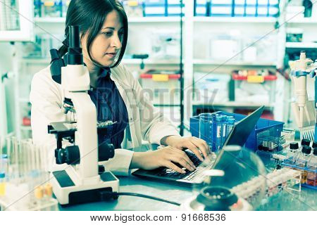 laboratory assistant analyzes of DNA sequence on the computer