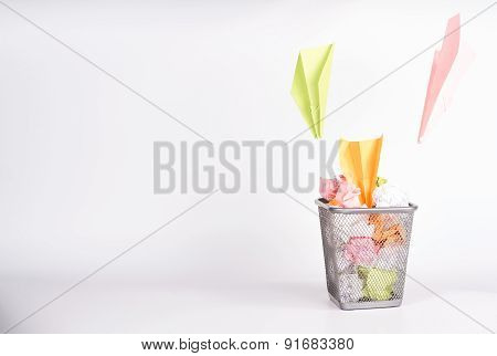 isolated wastebasket full of color waste paper and paper airplanes poster