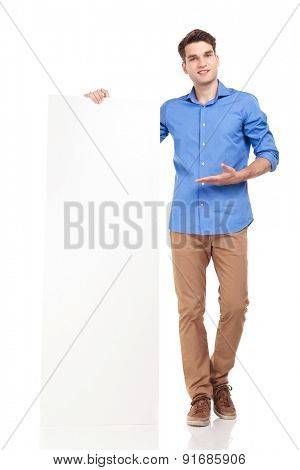 Attractive young fashion man presenting a white board, while smling.