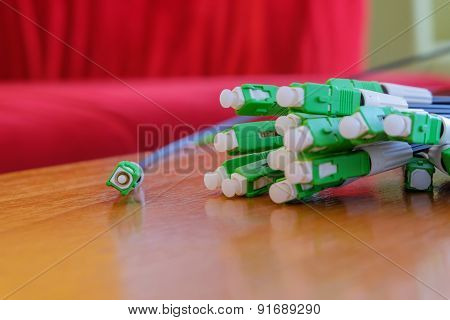 A group head connector fiber optic green color on brown table.Fiber Optics connectors. Internet Serv