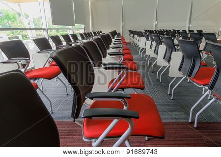 Many dark red chairs arranged neatly in a training room.
