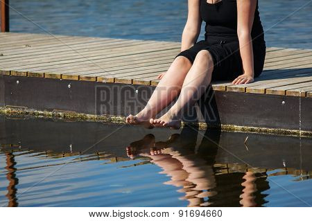 Young Lady Sitting On The Jetty
