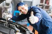 Portrait of an auto mechanic at work on a car in his garage poster
