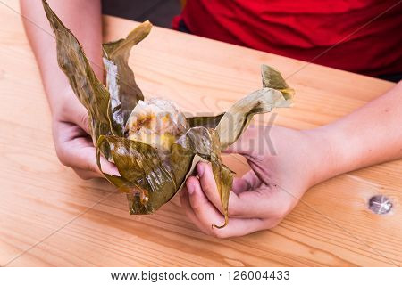 Hand Unwrapping Chinese Rice Dumpling Or Zongzi On Table