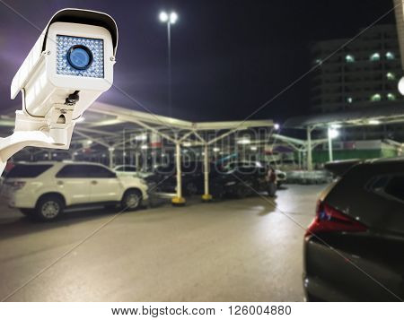 The CCTV Security Camera operating in parking lot car at night time blur background, CCTV Camera concept, CCTV Camera background, CCTV Camera idea, CCTV Camera copy space, CCTV Camera video.