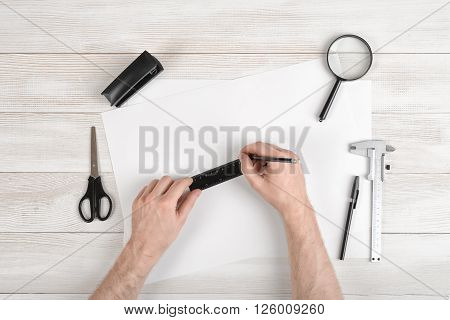 Workplace of draftsman equipped with pencil, ruler, pen, stapler, scissors and magnifying glass. Hands of man holding centimeter ruler and draw on white paper. Top view.