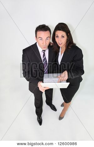 Man and businesswoman amazed in front of a laptop computer