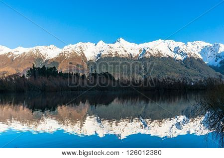 Mountain valley view. Nature landscape background photo of snow covered mountains reflected in blue water Otago New Zealand. Beautiful mountain valley winter landscape