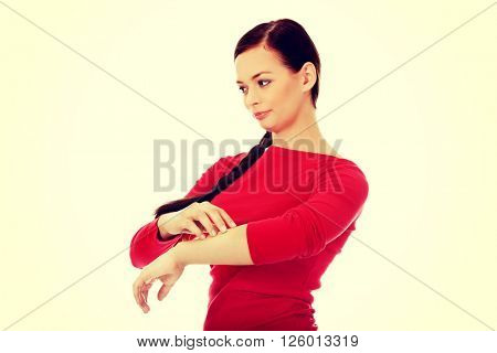 Young woman scratching her hand