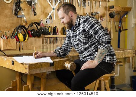 Adult craftsman sits and looks at plan drawings in a work shop for wood work and construction. Carpenter designs and prepares new work.